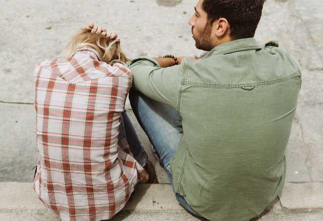 man and woman sitting on sidewalk 226166